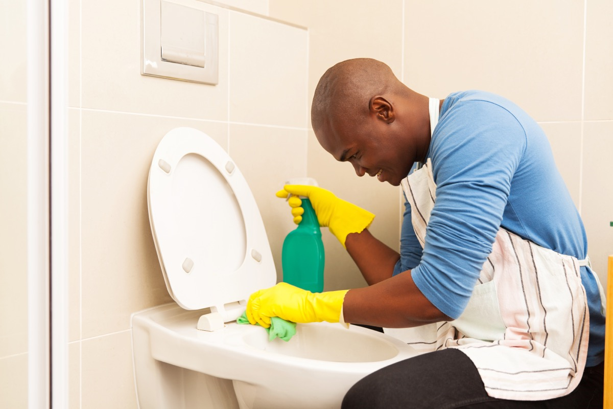 Man cleaning toilet with spray