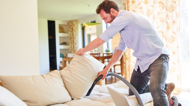 Man vacuuming couch cushions