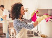 Woman cleaning kitchen shelf