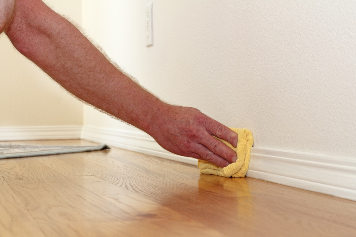 Man cleaning baseboard with cloth