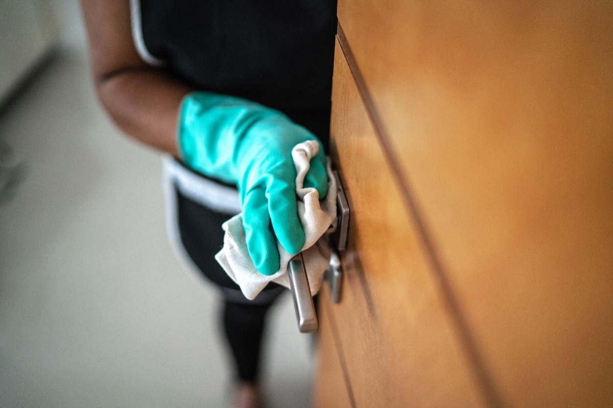 Hands with glove wiping doorknob