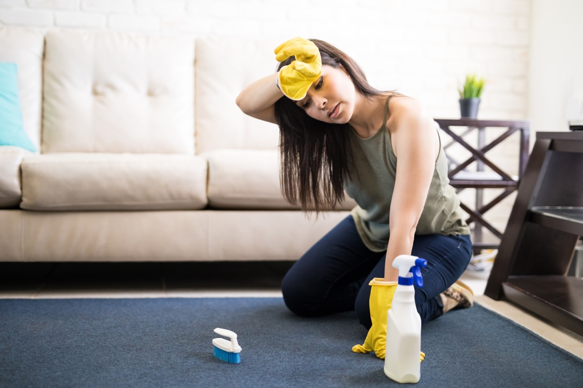 Young woman rubbing head wearing casuals and yellow gloves cleaning carpet with liquid soap