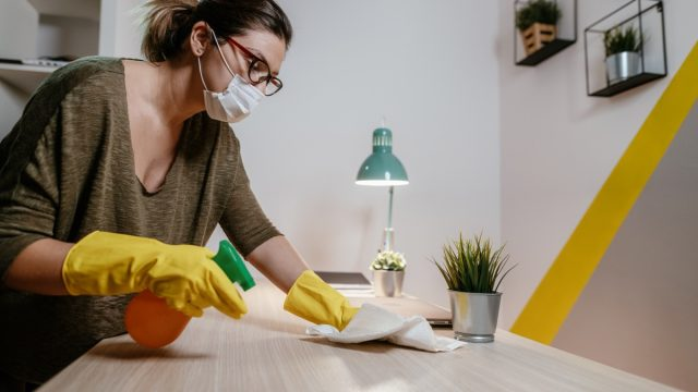 Woman with facial mask using antiseptic spay to clean the surface in home office