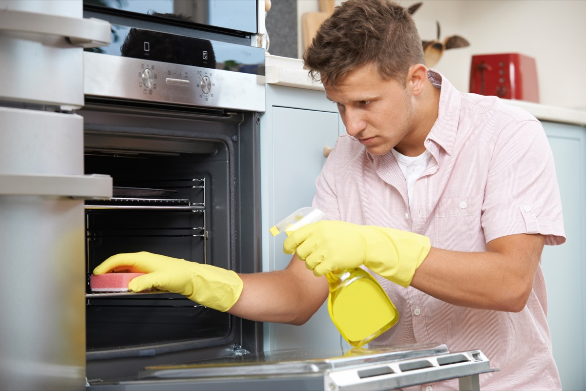 Man cleaning oven rack