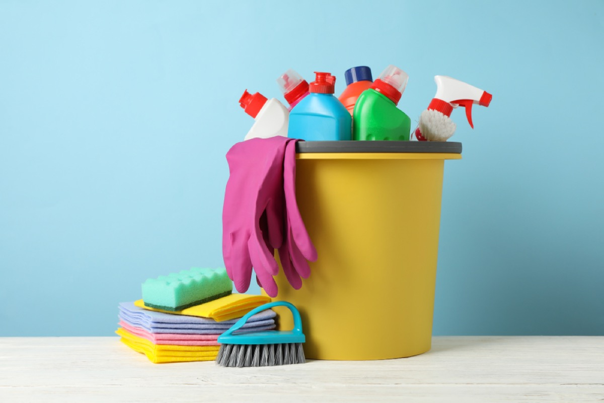 colorful cleaning supplies in yellow bucket on blue background