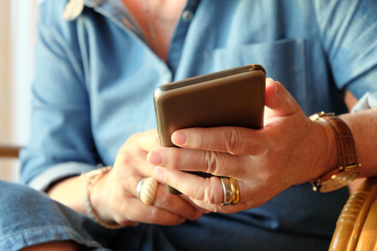 closeup of hands of older woman using smart phone