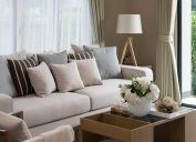 crowded living room with beige sofa