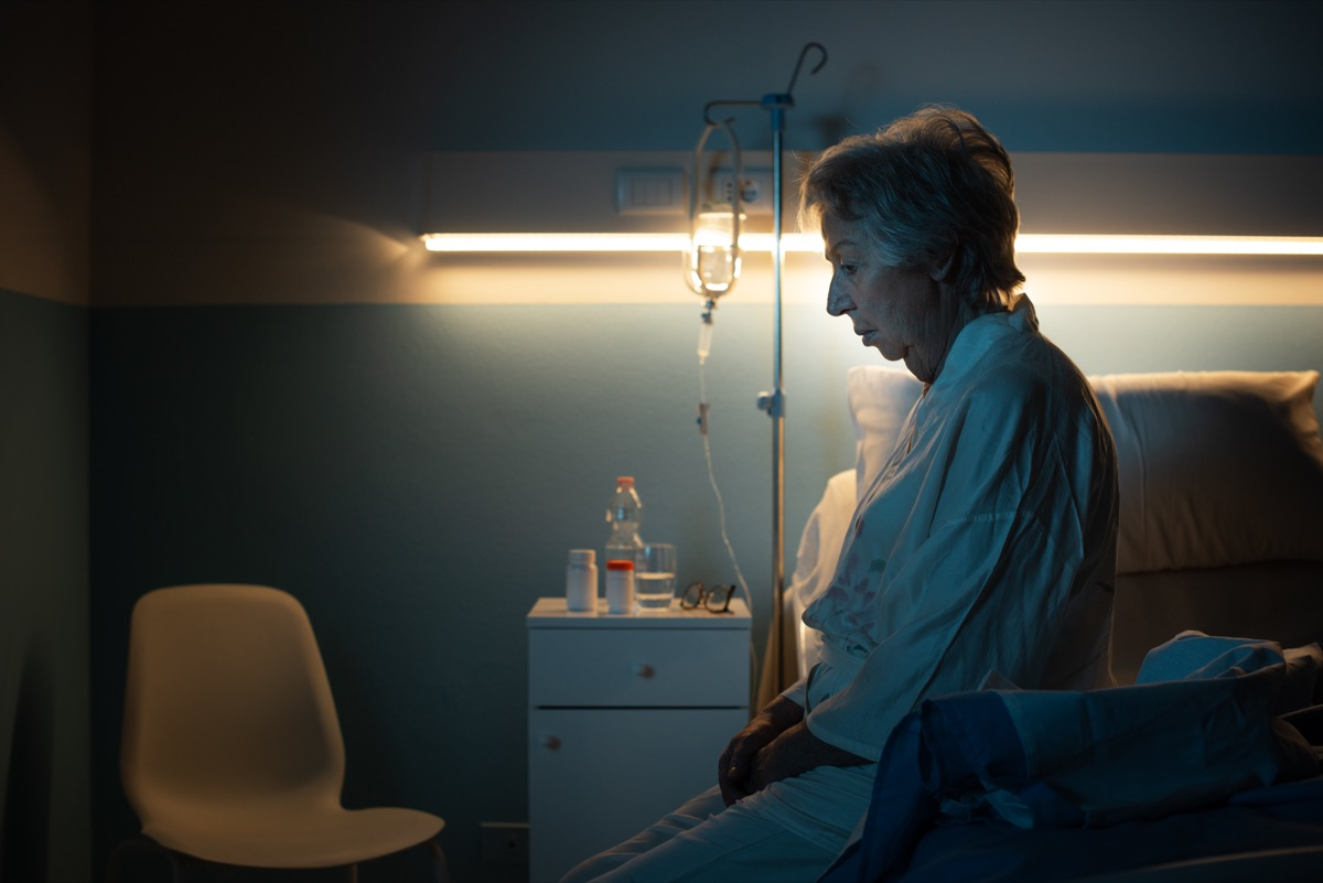 Woman sitting on the edge of a hospital bed confused