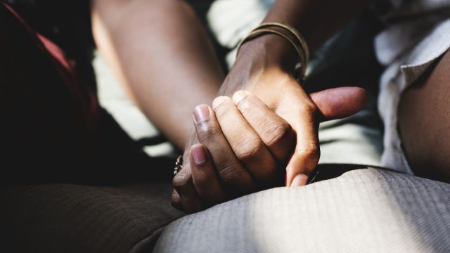 Closeup of couple holding hands on couch
