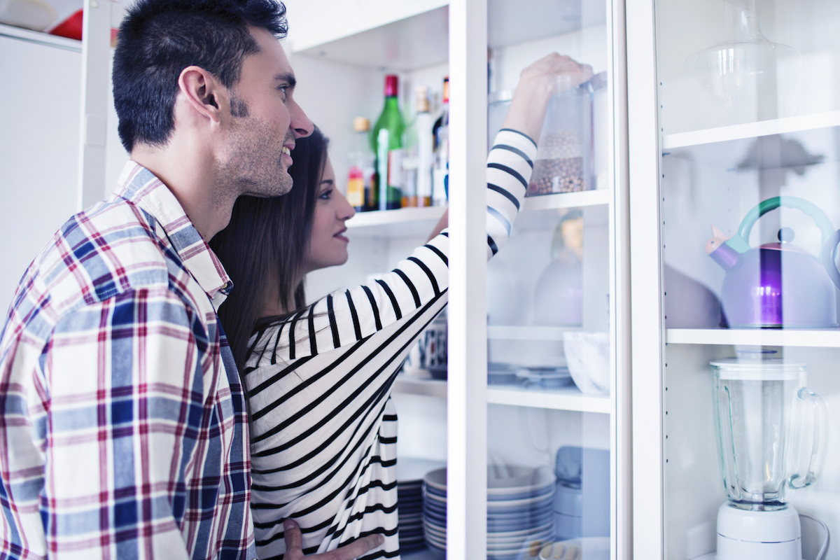 Young couple tidying up the kitchen cabinets
