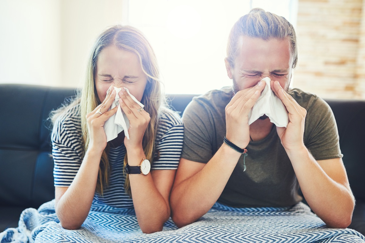 Shot of a young man and woman blowing their noses with tissue at home
