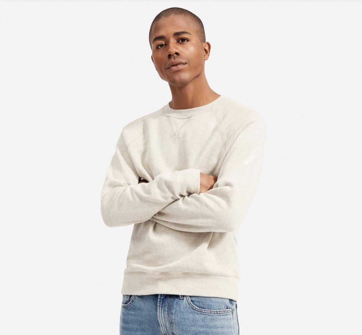 young black man in cream colored sweatshirt