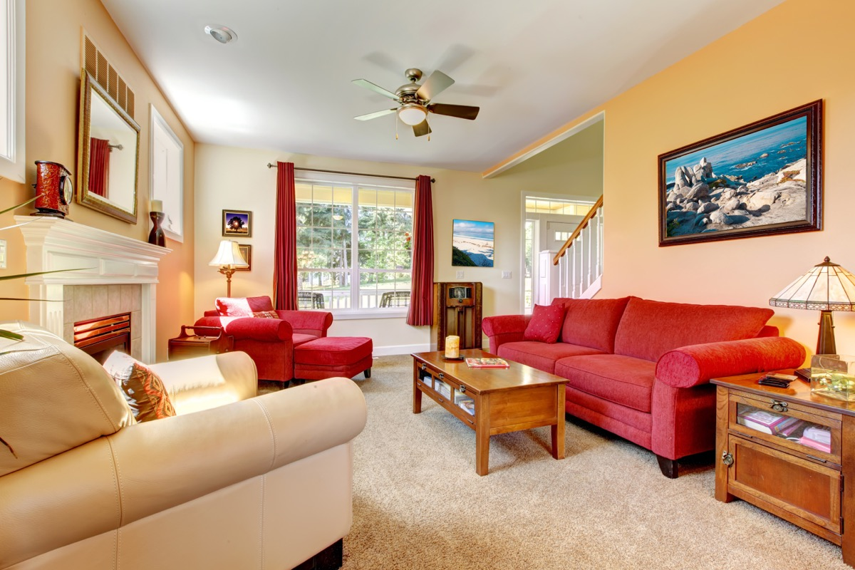 crowded living room with red furniture