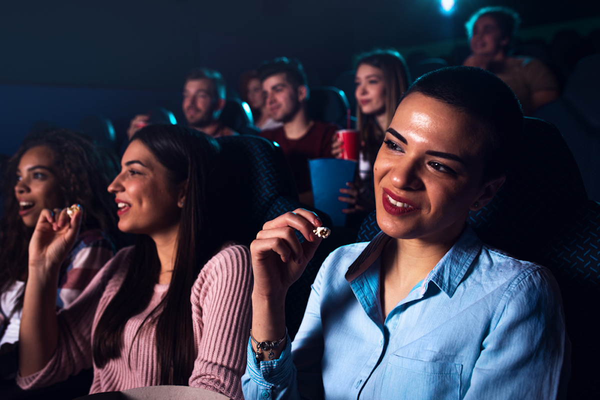 women in front row of crowded movie theater