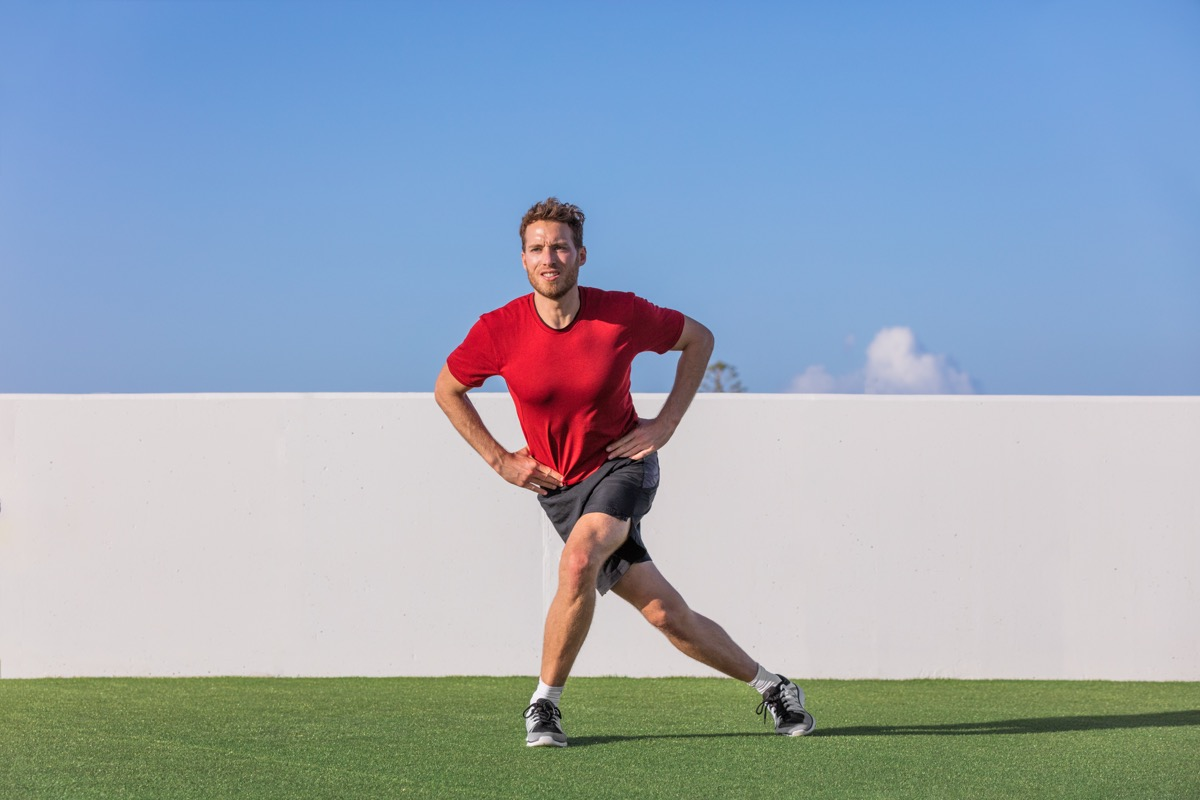 Man doing curtsy lunge