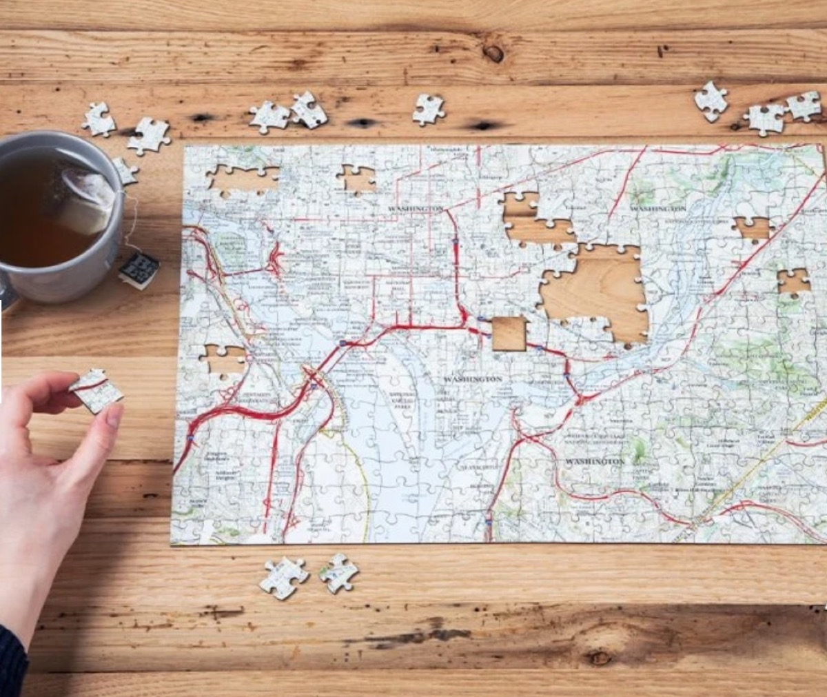 white hand putting together map jigsaw puzzle