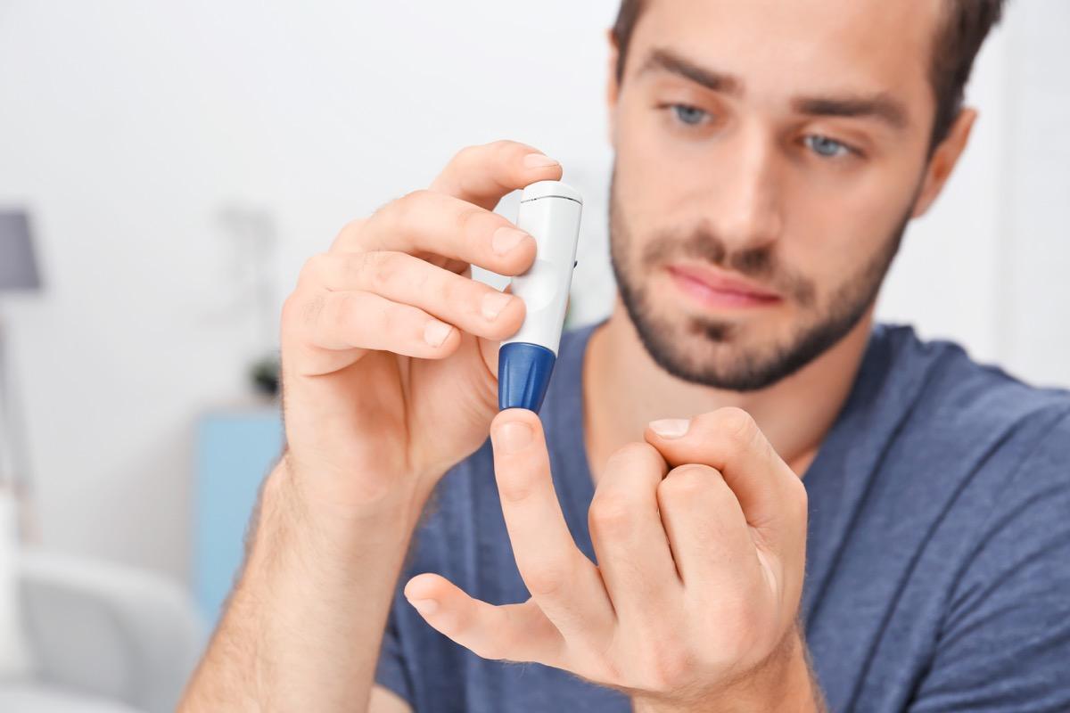 Man with diabetes pricking finger