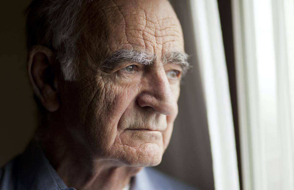 senior man staring out window