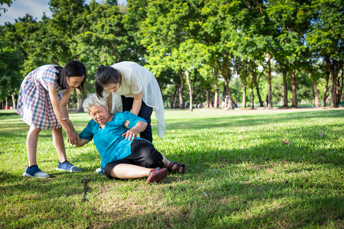 senior asian woman falls down in park, helped by granddaughters