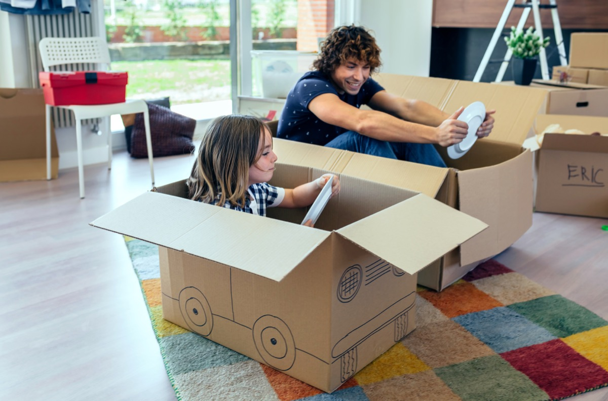 Father and son playing car racing with cardboard boxes in the living room