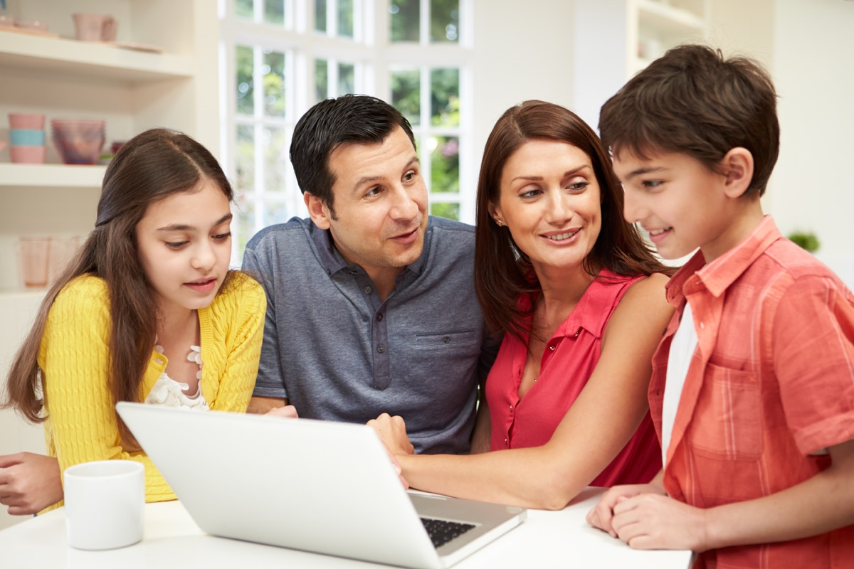 Family looking at laptop and talking in kitchen
