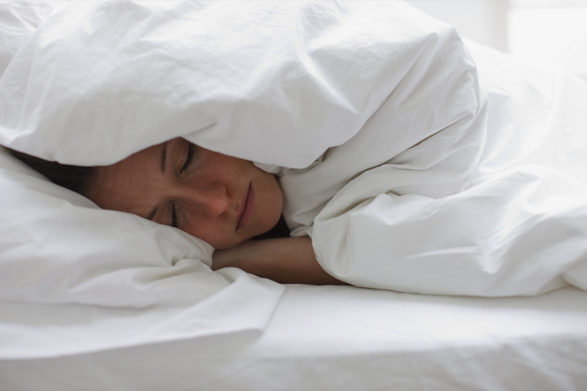 sick woman wrapped up in blankets