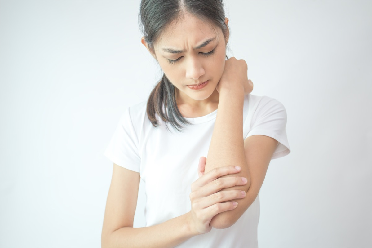Woman holding and examinging her arm in discomfort