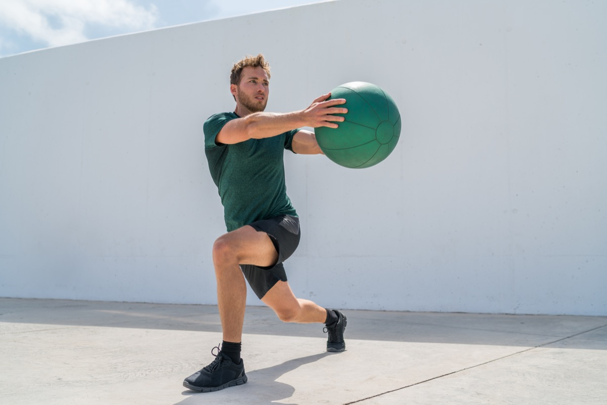 Man doing forward lunge with rotation and ball