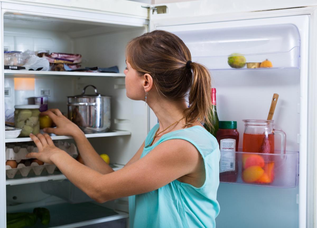Woman going through fridge