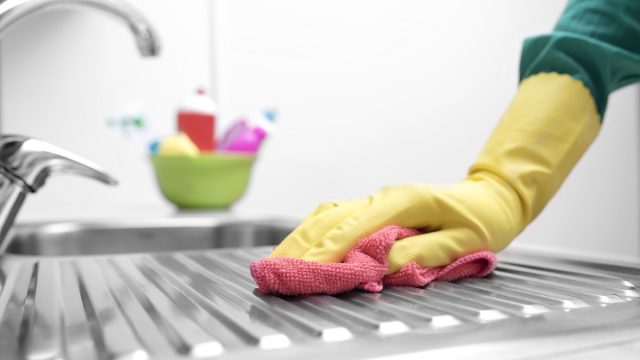 hand in yellow gloves cleaning kitchen