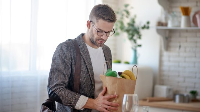 Man unpacking bag of groceries