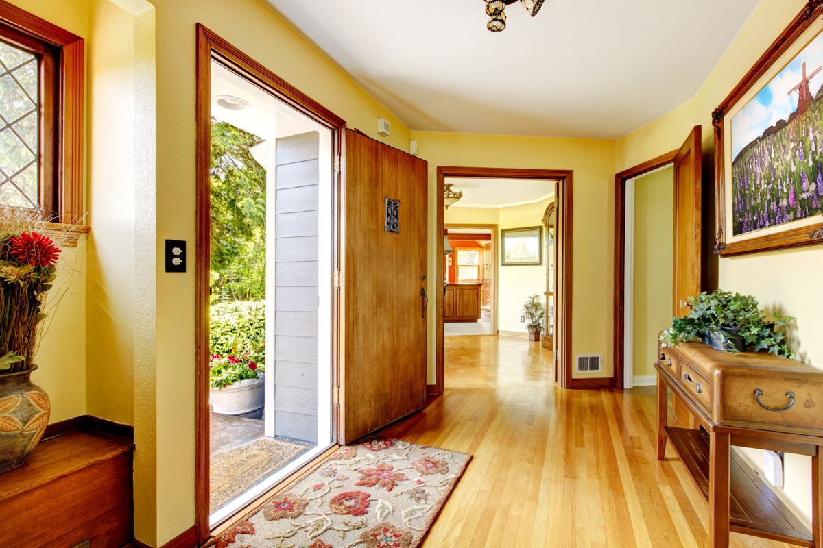 yellow hallway with furniture in it