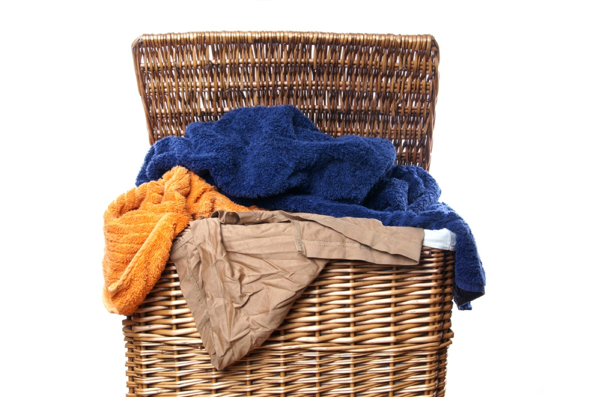 wicker hamper of dirty laundry on white background