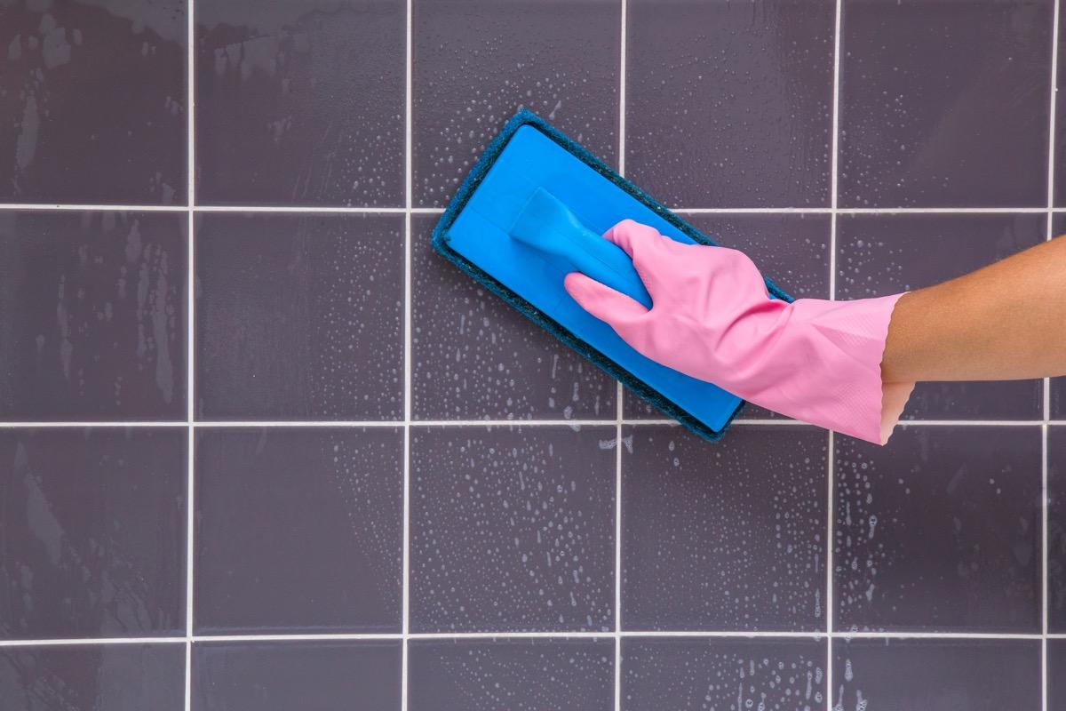 pink gloved hand scrubbing shower