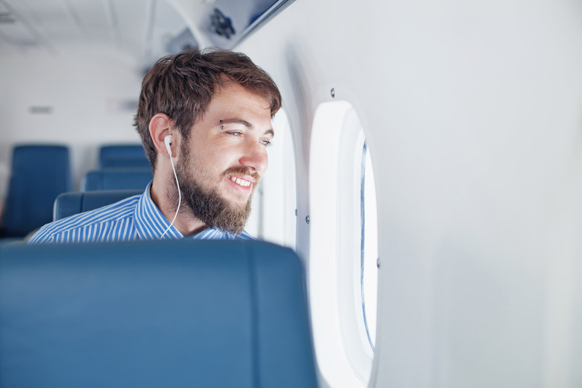 man looking out window of airplane while wearing headphones