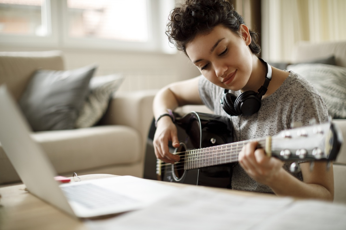 young girl playing guitar while looking at her computer