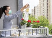 woman wearing a face mask and holding up wet cloth while doing laundry on the balcony
