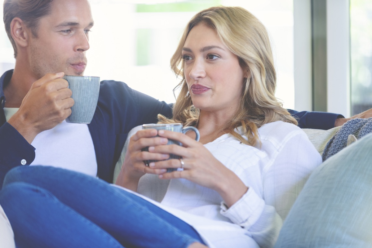 white woman looking uncomfortable while sharing coffee with white man on couch