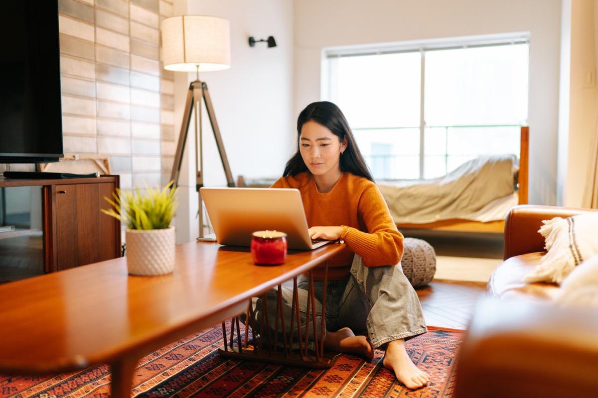 young asian woman using her laptop at the table at home
