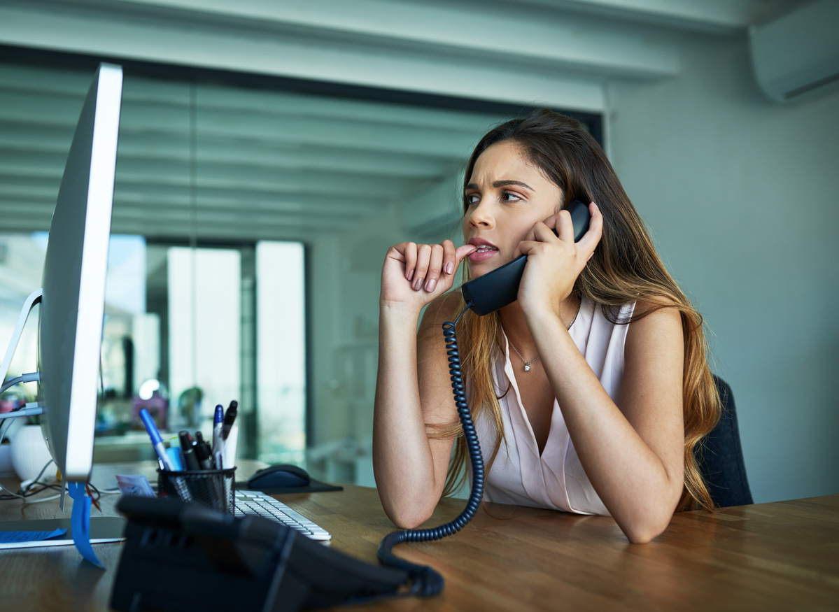 woman biting her nails while on the phone in front of a computer
