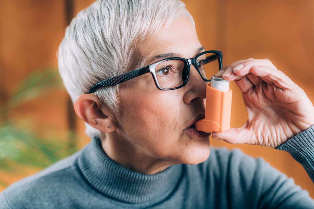 Woman taking puff of inhaler