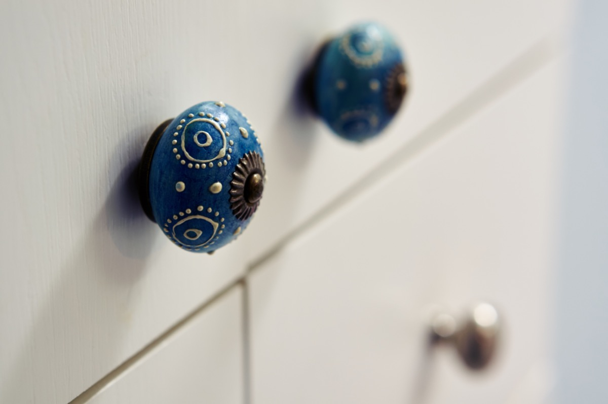 interesting blue cabinet knobs on a white cabinet