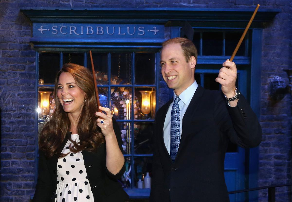 Kate Middleton and Prince William hold wands at the royal visit to Warner Bros Studios in 2013