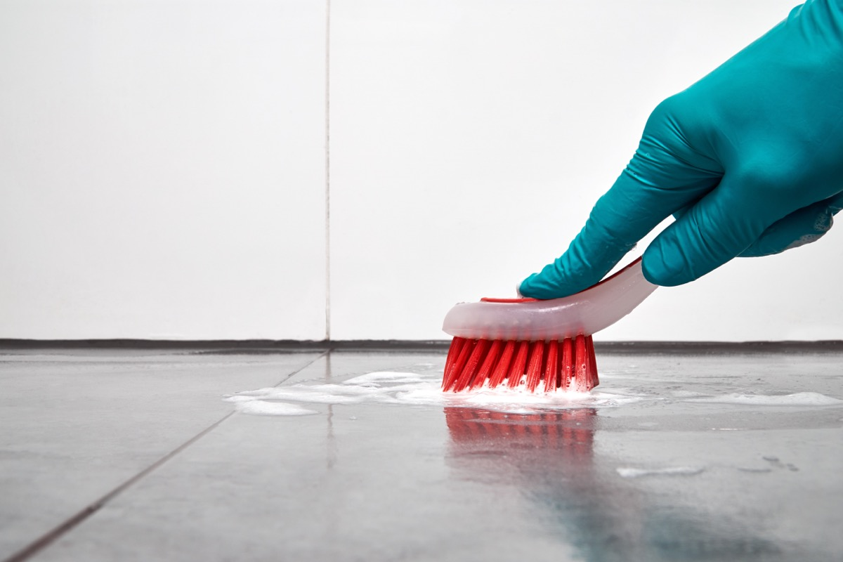 Scrubbing kitchen floor with brush