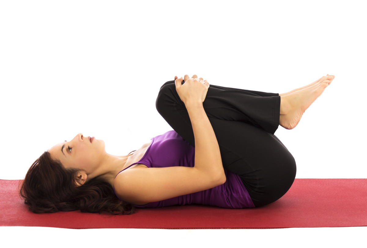 Woman laying stretching knees to chest on floor