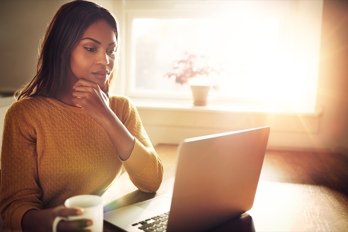 Woman thinking at her desk with laptop