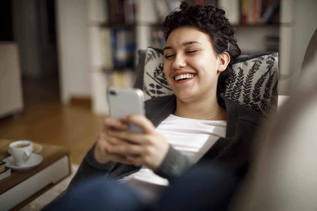 Young woman enjoying a relaxing weekend at home laughing while on phone