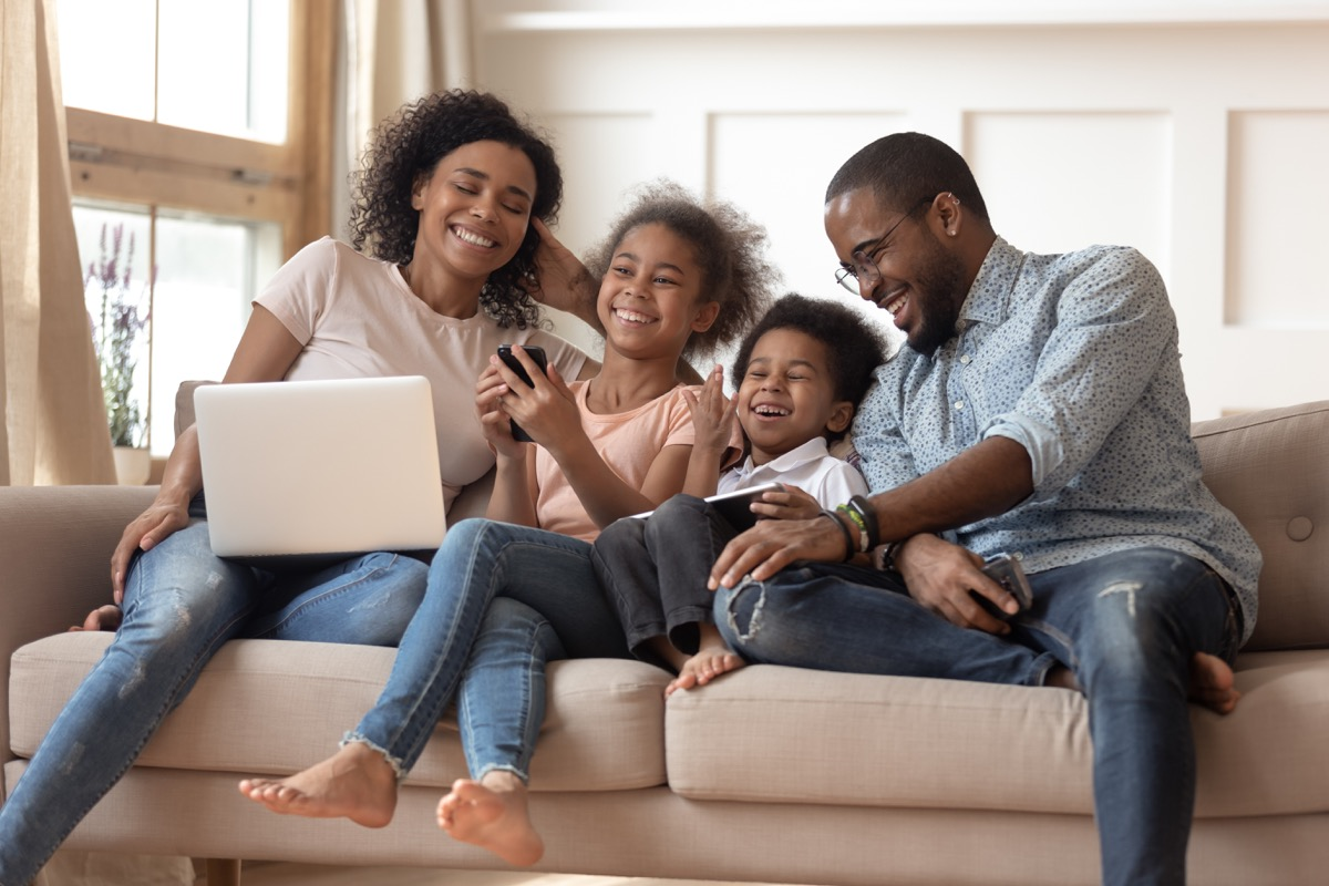 Family laughing on couch together