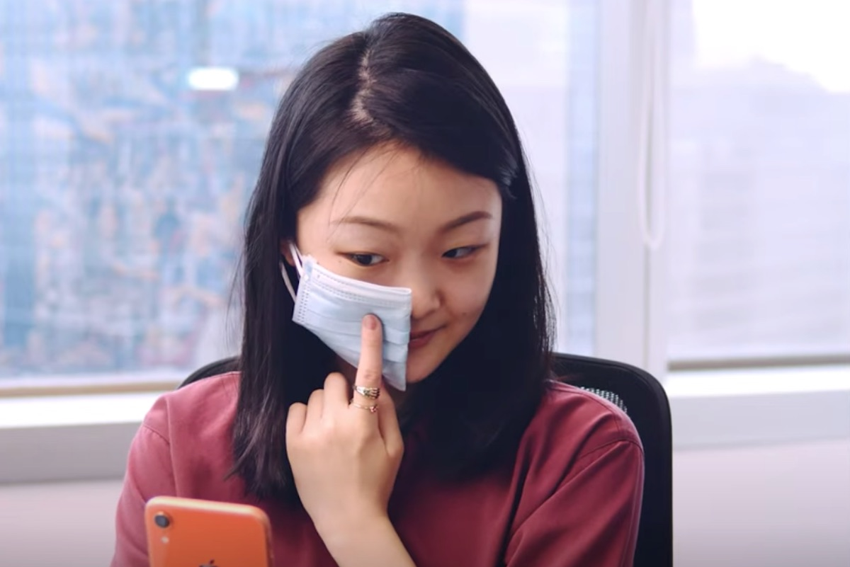 woman holding up face mask on left side of face