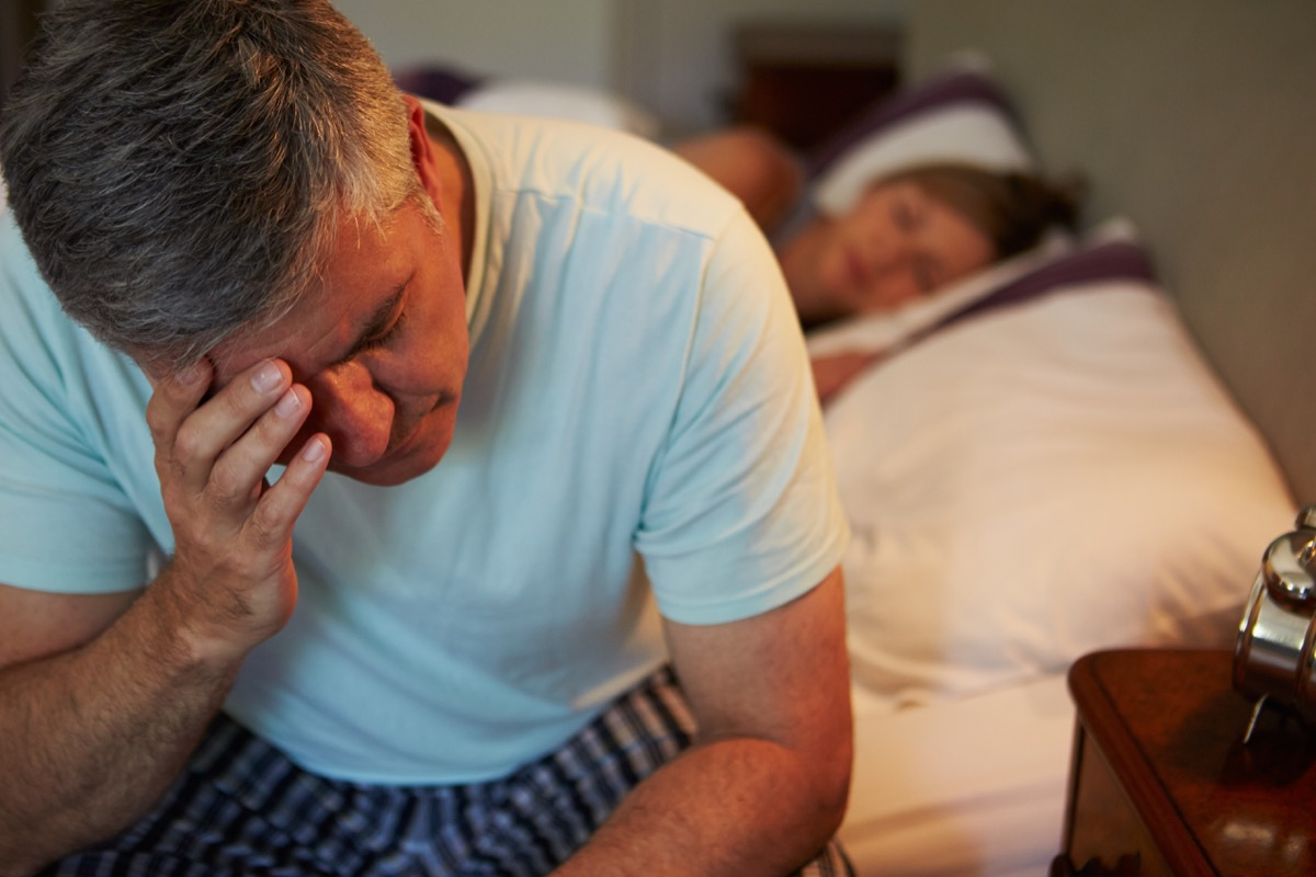 Man stressed in bed suffering from low libido